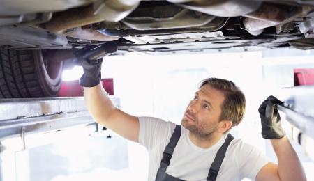 Man instpecting underneath a car