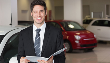 male car buying consultant holding paper work for customers new car